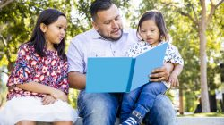 A mexican dad reads a book to his children. The young boy has down's syndrome.