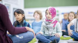A diverse group of preschool children are sitting on the ground cross-legged while meditating. They are practicing mindfulness as they face their teacher.